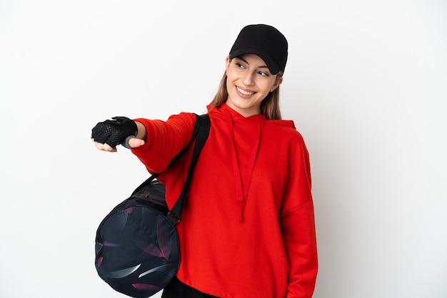 Mulher jovem esportiva com bolsa esportiva isolada no fundo branco fazendo um gesto de polegar para cima