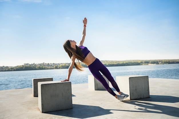 Mulher jovem esportiva fazendo exercícios de fitness perto do lago durante o dia. conceito de estilo de vida saudável
