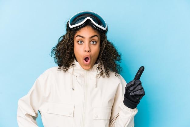 Mulher jovem esquiador americano africano isolado apontando para o lado