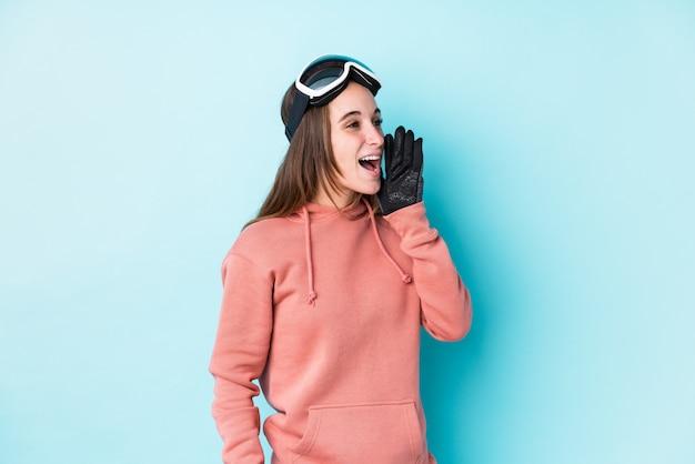 Mulher jovem esquiador gritando e segurando a palma da mão perto da boca aberta.