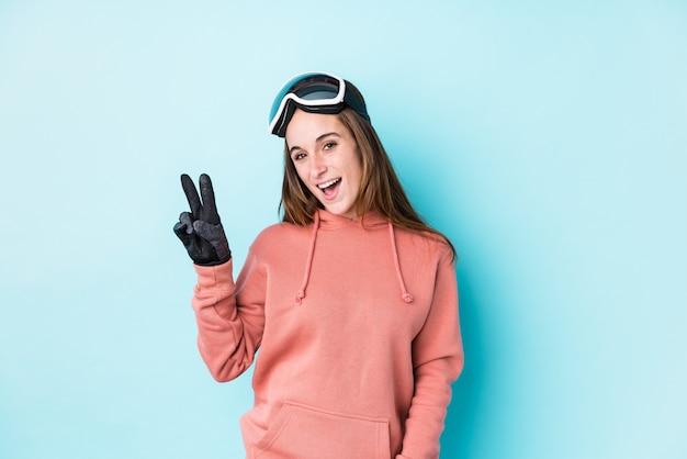 Mulher jovem esquiador isolado alegre e despreocupado, mostrando um símbolo de paz com os dedos.