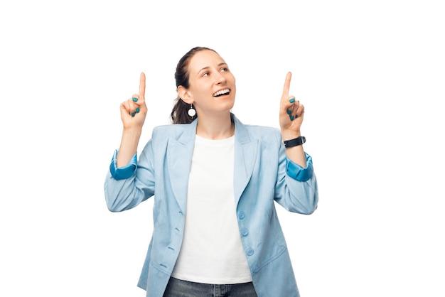 Mulher jovem está apontando para cima com as duas mãos e fazendo uma careta de espanto.