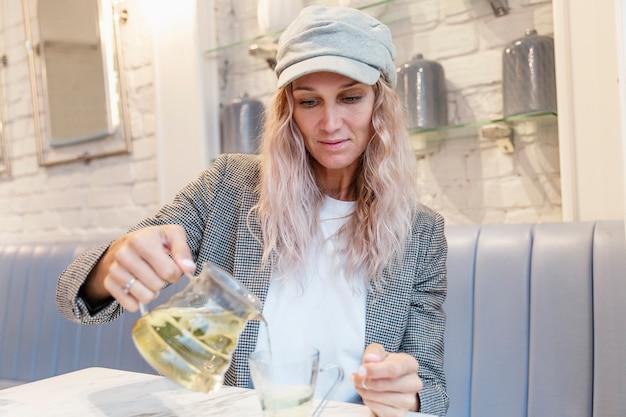 Mulher jovem está bebendo chá em um café