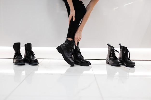 Mulher jovem está de pé em um shopping ao lado de sapatos em jeans pretos elegantes e botas pretas sazonais de couro preto da moda. coleção outono-primavera da moda de calçados femininos. close das pernas.