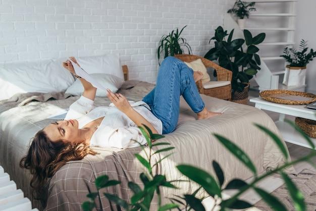 Mulher jovem está deitada em seu quarto lendo documentos.