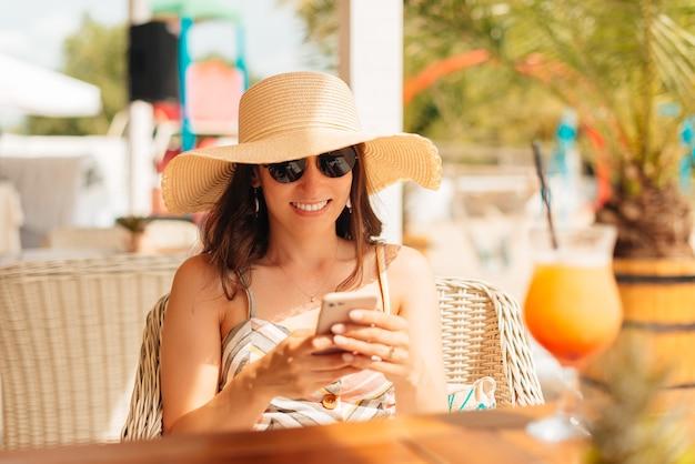 Mulher jovem está digitando no celular enquanto toma um coquetel.