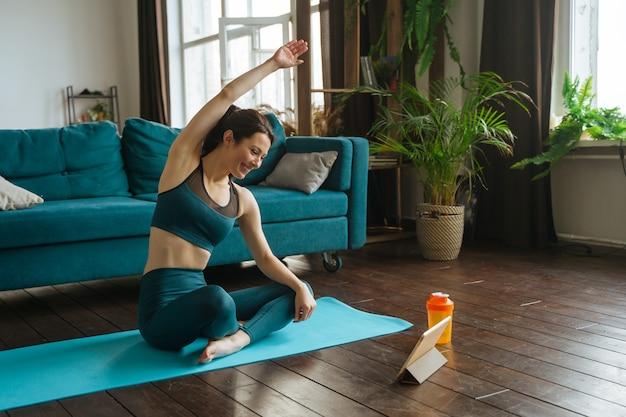 Mulher jovem está envolvida em exercícios físicos em casa, conversando com o treinador remotamente usando um tablet