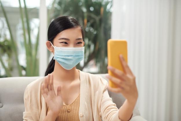 Mulher jovem está falando por videochamada na máscara. trabalhar em casa, conversar com amigos, tirar selfie com máscara
