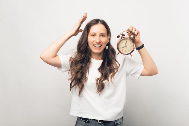 Mulher jovem está frustrada com a velocidade do tempo. retrato sobre fundo branco.