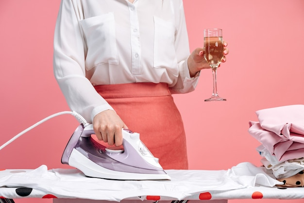 Mulher jovem está passando roupas na tábua de passar, segurando um copo na mão