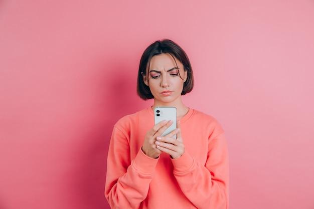 Mulher jovem está se sentindo triste, infeliz com raiva enquanto lê sms usando seu telefone celular, sobre o fundo rosa