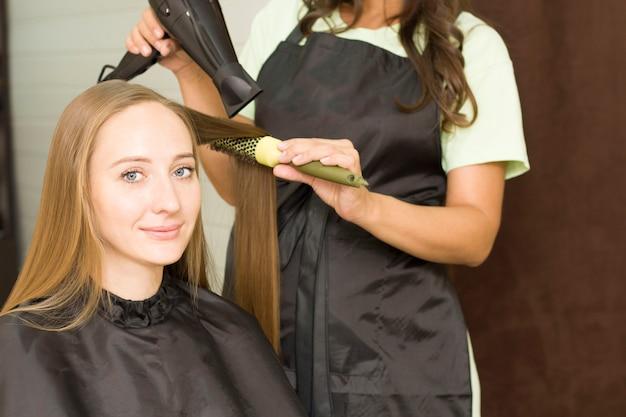 Mulher jovem está secando o cabelo com um secador de cabelo.