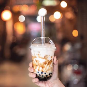Mulher jovem está segurando, bebendo açúcar mascavo com leite de bolha de pérola de tapioca, chá com canudo de vidro no mercado noturno de taiwan close up bokeh