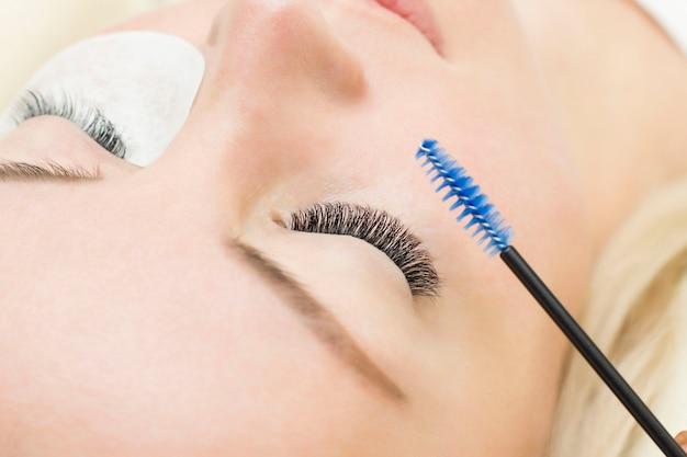 Mulher jovem está sendo submetida a um procedimento de extensão de cílios em close. escova de cílios