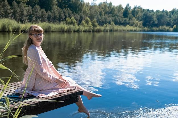 Mulher jovem está sentada em um píer de madeira no lago e mergulha os pés na água