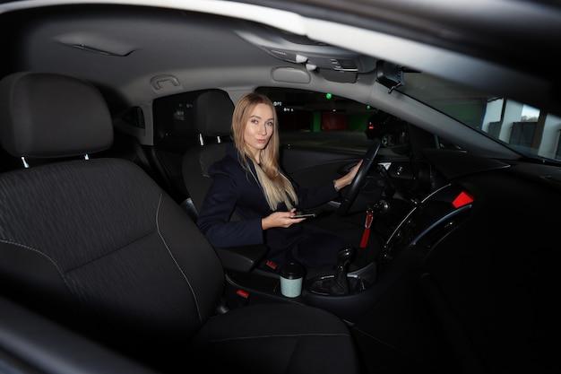 Mulher jovem está sentada no carro e digitando no telefone