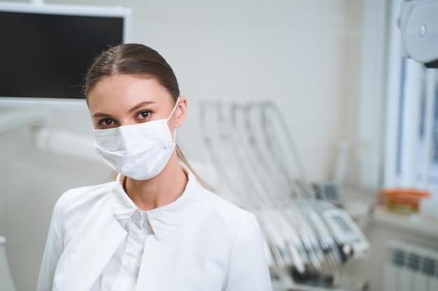 Mulher jovem está usando máscara estéril em pé na clínica antes da tela digital.