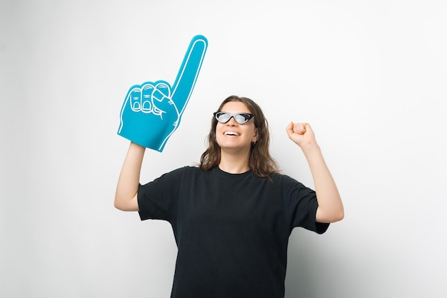 Mulher jovem está usando óculos escuros, luva de leque de espuma e fazendo o gesto de vencedor.