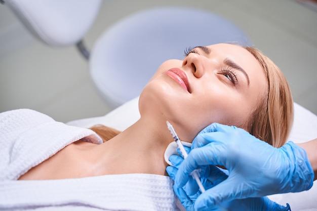 Mulher jovem está vendo cosmetologista para receber injeções de ácido hialurônico no rosto para rejuvenescimento