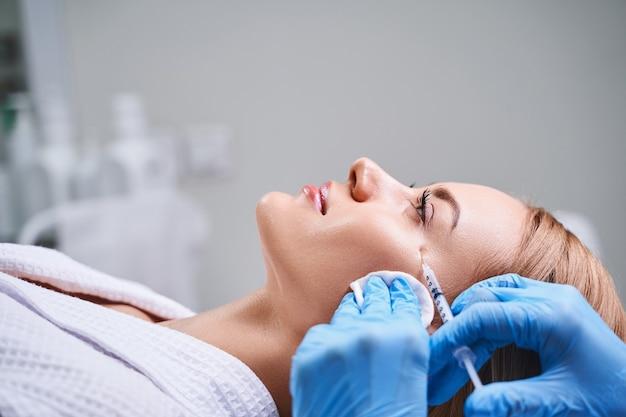 Mulher jovem está visitando uma cosmetologista e deitada no sofá enquanto um profissional está aplicando preenchimentos antiidade em seu rosto
