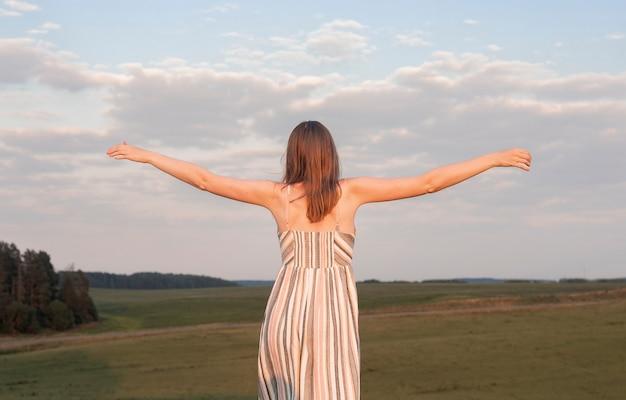 Mulher jovem estendendo os braços sobre o campo no verão, aproveitando a liberdade e a harmonia