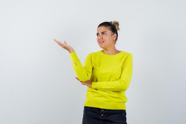 Mulher jovem esticando a mão e segurando algo enquanto segura a mão no cotovelo com suéter amarelo e calça preta e parece feliz