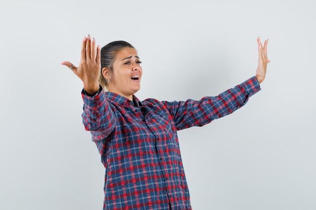 Mulher jovem, esticando as mãos como se convidando para entrar em uma camisa xadrez e parecendo feliz, vista frontal.