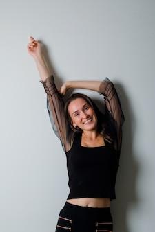 Mulher jovem esticando as mãos e sorrindo graciosamente em uma blusa preta e calça preta e com uma aparência charmosa