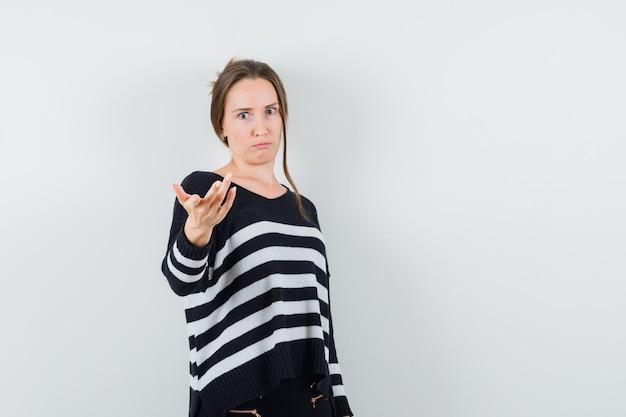 Mulher jovem esticando as mãos para a frente com blusa e calça pretas e parecendo surpresa