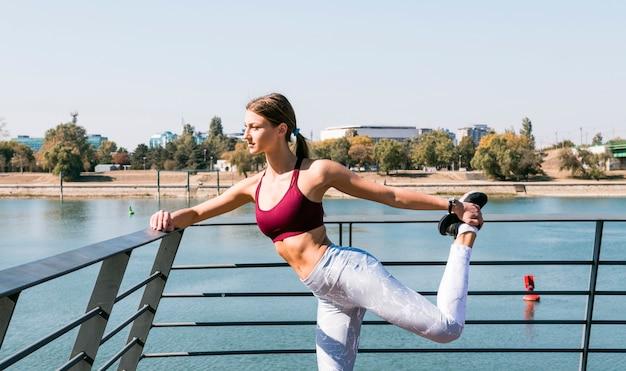 Mulher jovem, esticar, e, exercitar, ao ar livre