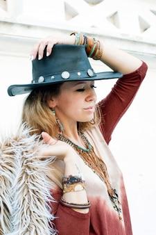Mulher jovem estilo hippie vestida com um chapéu preto de couro ecológico com um casaco de pele feito de pele ecológica