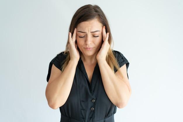 Mulher jovem estressada cansada no vestido preto sentindo dor de cabeça e massageando templos.