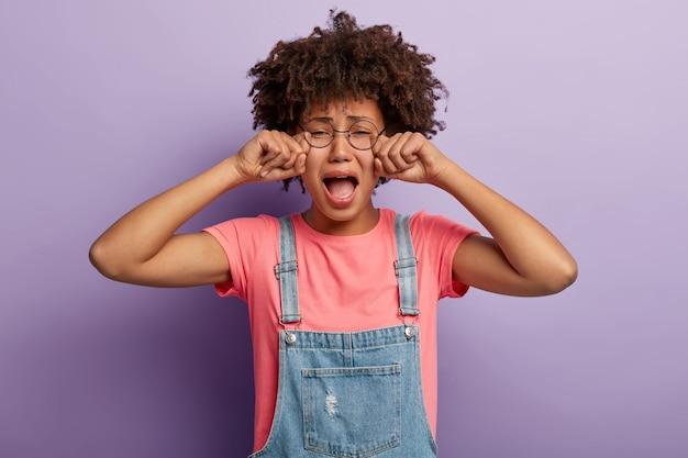 Mulher jovem estressada com um afro posando de macacão