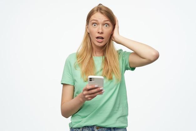 Mulher jovem estressada e chocada, com cabelos longos loiros, mantém a mão na cabeça, segura o telefone com os olhos arregalados e expressão facial confusa