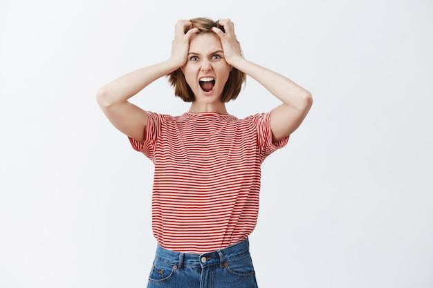Mulher jovem estressada e tensa agarra a cabeça e grita, entrando em pânico com alguma coisa, parecendo com raiva