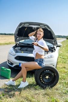 Mulher jovem estressada olhando para o motor do carro dela. problemas de viagem. o carro precisa de conserto.