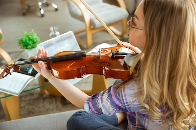 Mulher jovem estudando em casa durante cursos online ou informações gratuitas por conta própria. torna-se músico, violinista enquanto isolado, quarentena contra a propagação do coronavírus. usando laptop, smartphone.