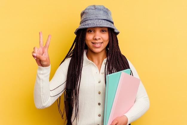 Mulher jovem estudante afro-americana mostrando o número dois com os dedos.