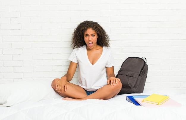 Mulher jovem estudante afro-americano na cama gritando muito irritado e agressivo