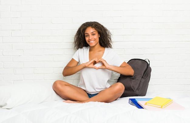 Mulher jovem estudante afro-americano na cama sorrindo e mostrando uma forma de coração com as mãos.