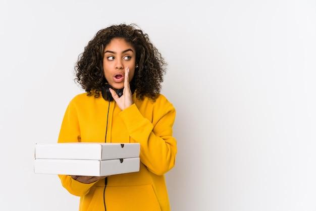 Mulher jovem estudante afro-americano segurando pizzas está dizendo uma notícia secreta de travagem quente e olhando de lado