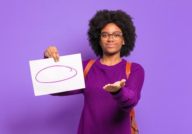 Mulher jovem estudante afro sorrindo alegremente com um olhar amigável, confiante e positivo, oferecendo e mostrando um objeto ou conceito