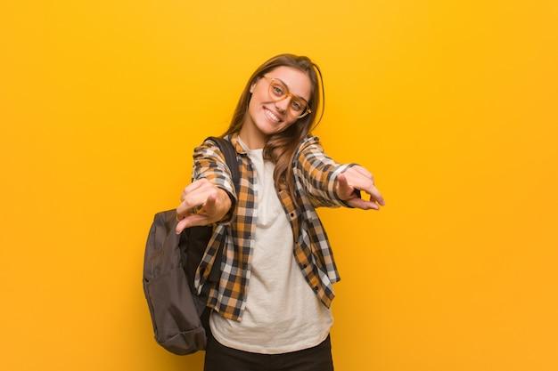 Mulher jovem estudante alegre e sorridente apontando