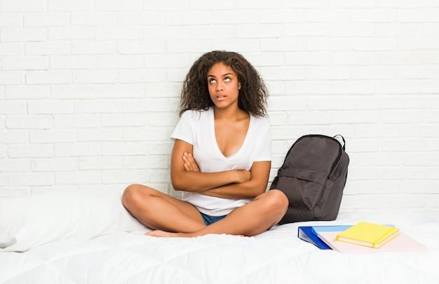 Mulher jovem estudante americano africano na cama cansada de uma tarefa repetitiva.
