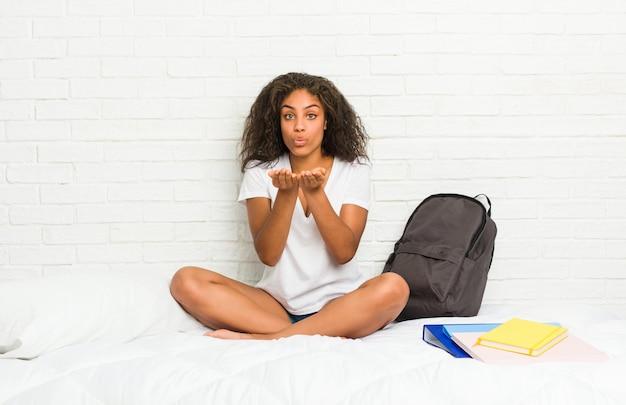 Mulher jovem estudante americano africano na cama dobrar os lábios e segurando as palmas das mãos para enviar beijo de ar.