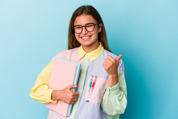 Mulher jovem estudante caucasiana segurando livros isolados em um fundo azul, sorrindo e levantando o polegar