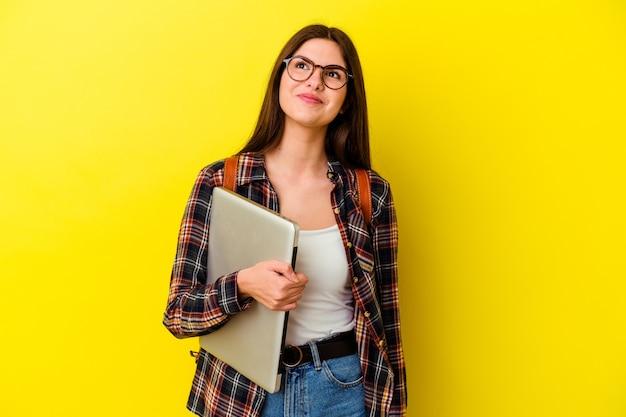Mulher jovem estudante caucasiana segurando um laptop rosa, sonhando em alcançar objetivos e propósitos