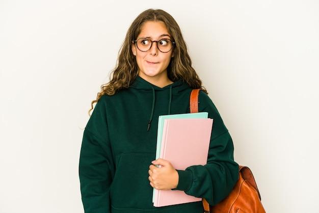 Mulher jovem estudante caucasiano isolada confusa, sente-se em dúvida e insegura.