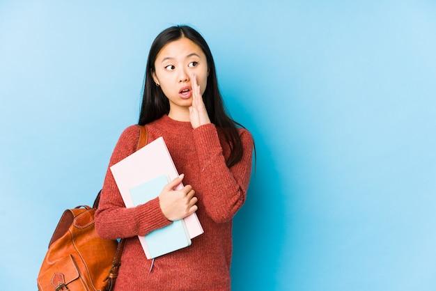 Mulher jovem estudante chinês isolado está dizendo uma notícia secreta de travagem quente e olhando de lado
