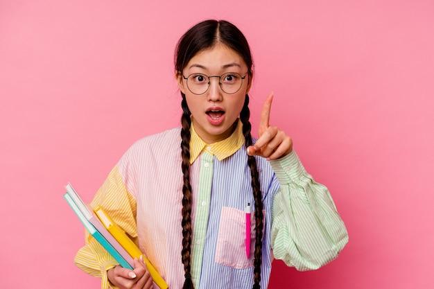 Mulher jovem estudante chinesa segurando livros vestindo uma camisa multicolorida de moda e uma trança, isolada no fundo rosa, tendo uma ideia, o conceito de inspiração.